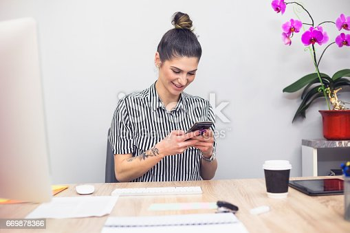 518704237 istock photo Young tattoo business woman in office 669878366