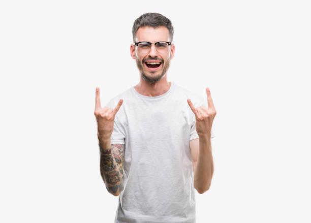 young tätowiert erwachsenen mann schreien mit verrückten ausdruck rock symbol mit händen bis zu tun. musik-star. schwere konzept. - sternenkinder tattoo stock-fotos und bilder