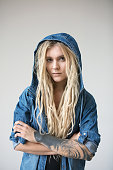 Young tattooed and pirced woman with blond dreadlocks and hoody