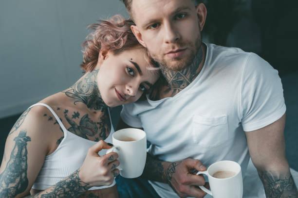 junge tätowierte paar blick in die kamera und tranken kaffee im bett am morgen - kaffeetasse tattoo stock-fotos und bilder