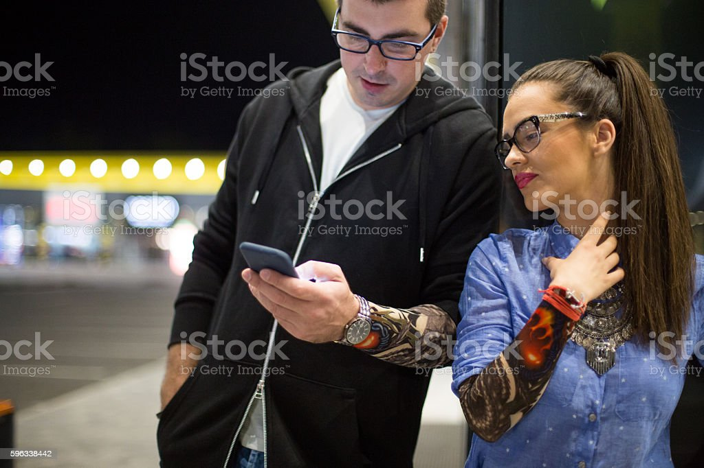 Young Tattooed Couple using smartphone royalty-free stock photo