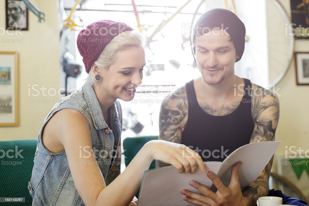 young tattooed man and woman looking at catalogue stock photo