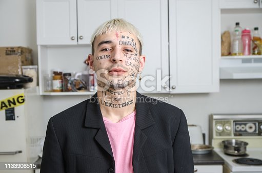 Young tattooed man posing in his kitchen