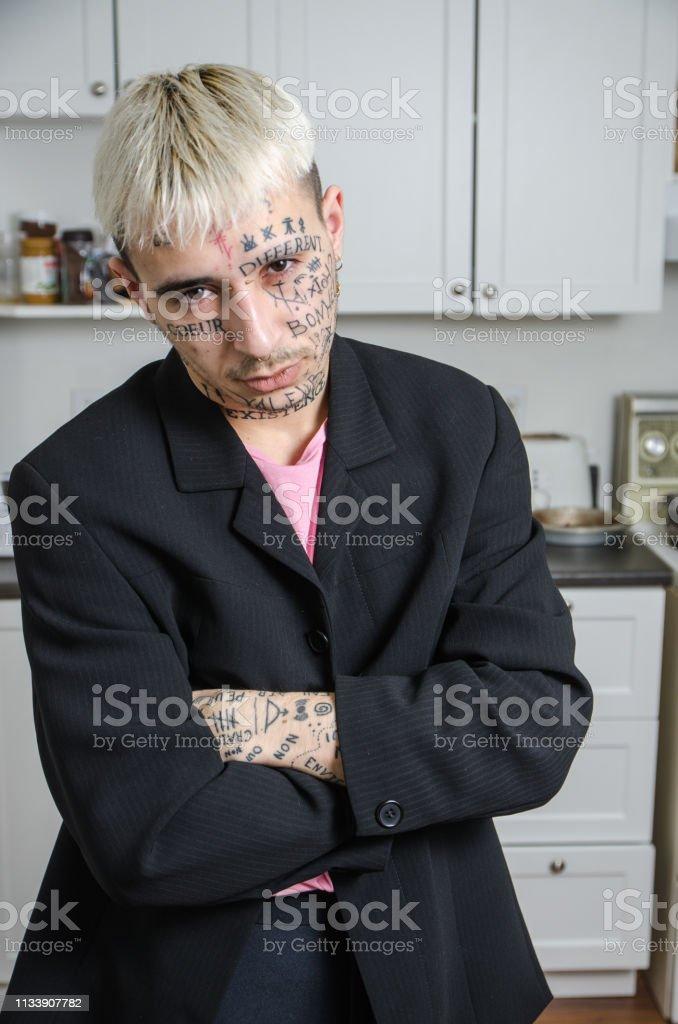 Junger tätowierer Mann posiert in seiner Küche – Foto