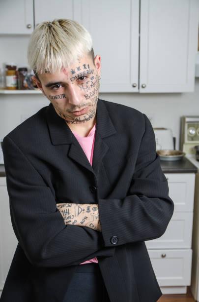 young tattooed man posing in his kitchen - capelli ossigenati foto e immagini stock