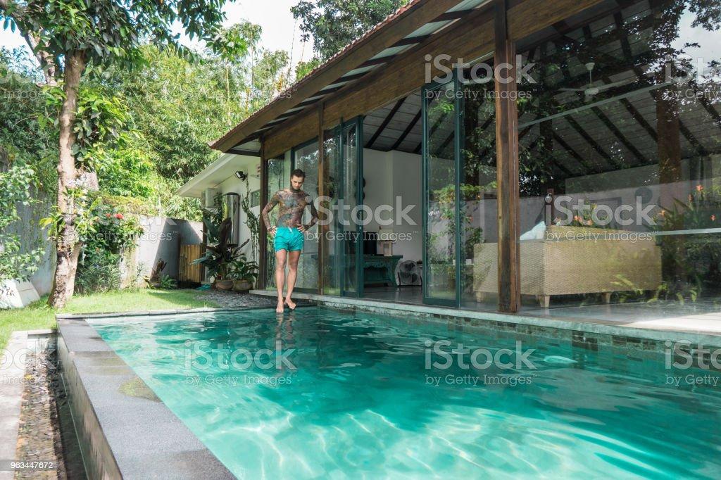 Yüzme Havuzu bali, Endonezya tatil sırasında ayakta genç dövmeli adam - Royalty-free Adamlar Stok görsel