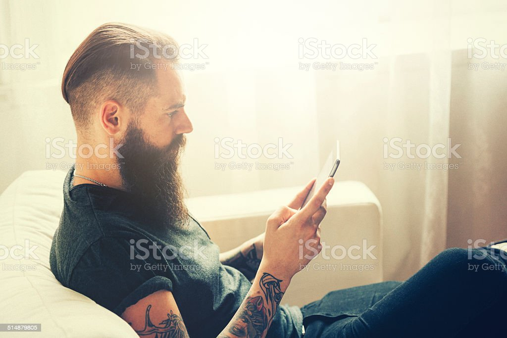 young tattooed man using tablet stock photo