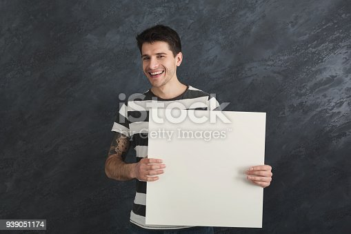 1048561956 istock photo Young tattooed man with blank white paper 939051174