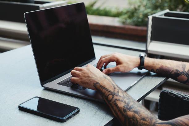 junge tätowierte mann arbeitet auf laptop in einem café. rückansicht von hipster-händen mit tattoo beschäftigt mit laptop am coworking büro schreibtisch. guy tippt text auf laptop mit leeren kopie space bildschirm mockup - tatto vorlagen stock-fotos und bilder