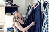 Young tattooed woman choosing clothes in her dress room