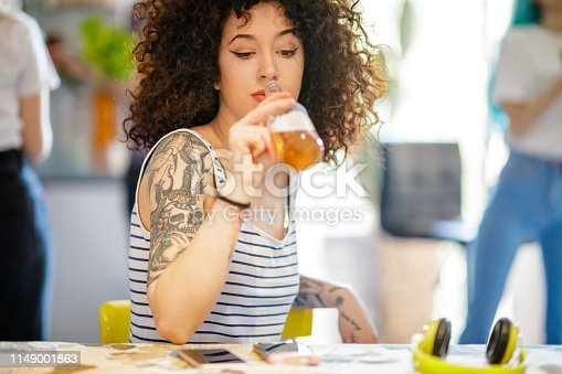 Young tattooed woman sitting at kitchen table and having beer, flatmates in the back