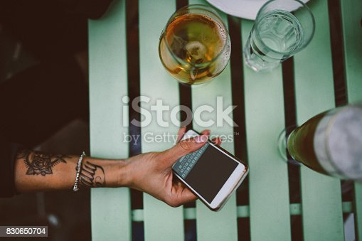 Overhead high angle view image of young woman's hands with tattoos, having a drink in the cafe outdoors, and checking messages on her smartphone.
