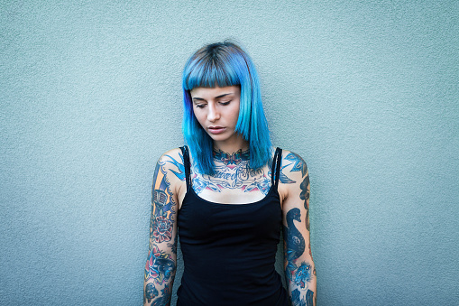 istock Young tattooed women with blue hair 654287560