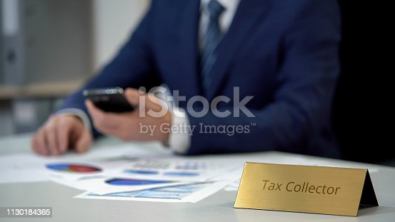 istock Young tax collector with phone checking debt statistics in diagram documents 1130184365