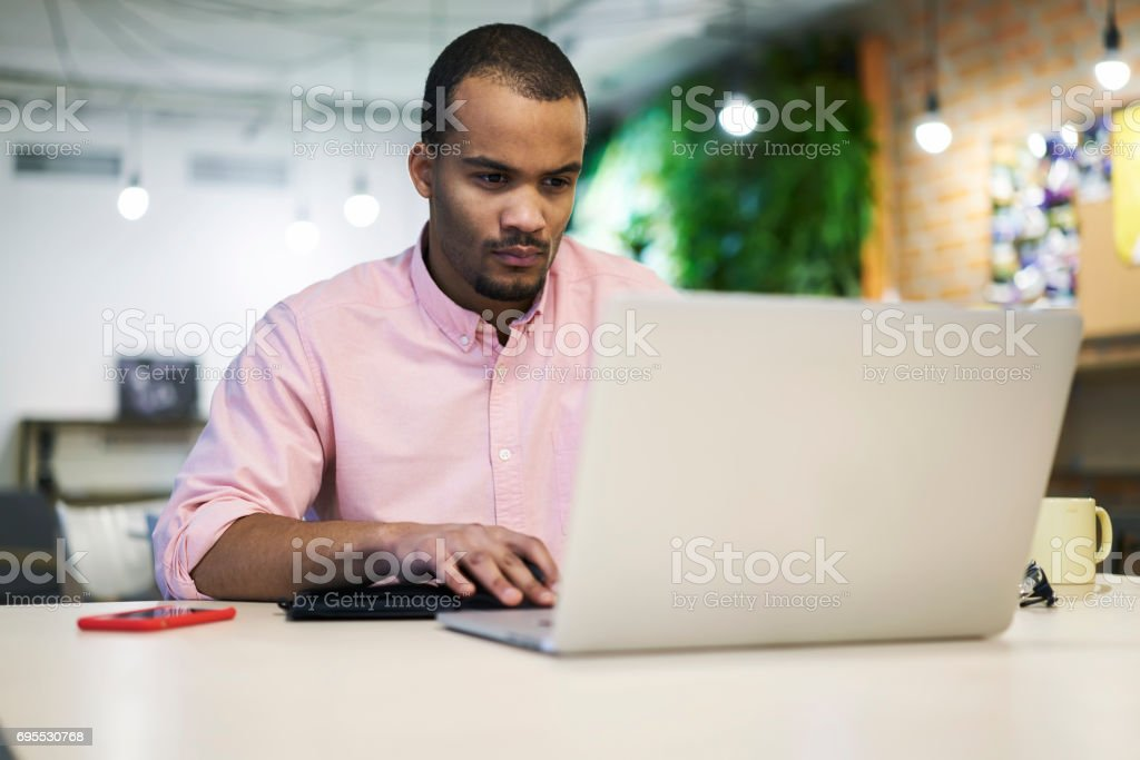 Young teacher and student correcting bugs online chatting using free wireless internet connection stock photo