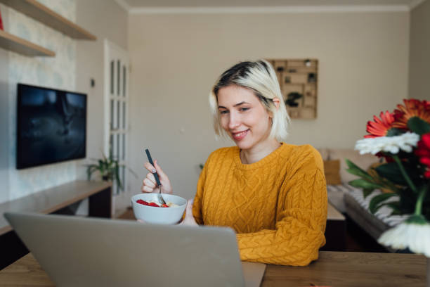 Young teacher having an online class and eating breakfast stock photo
