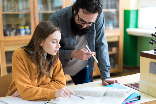 Young teacher helping his student in chemistry class. Education, Tutoring and Encouragement concept. stock photo