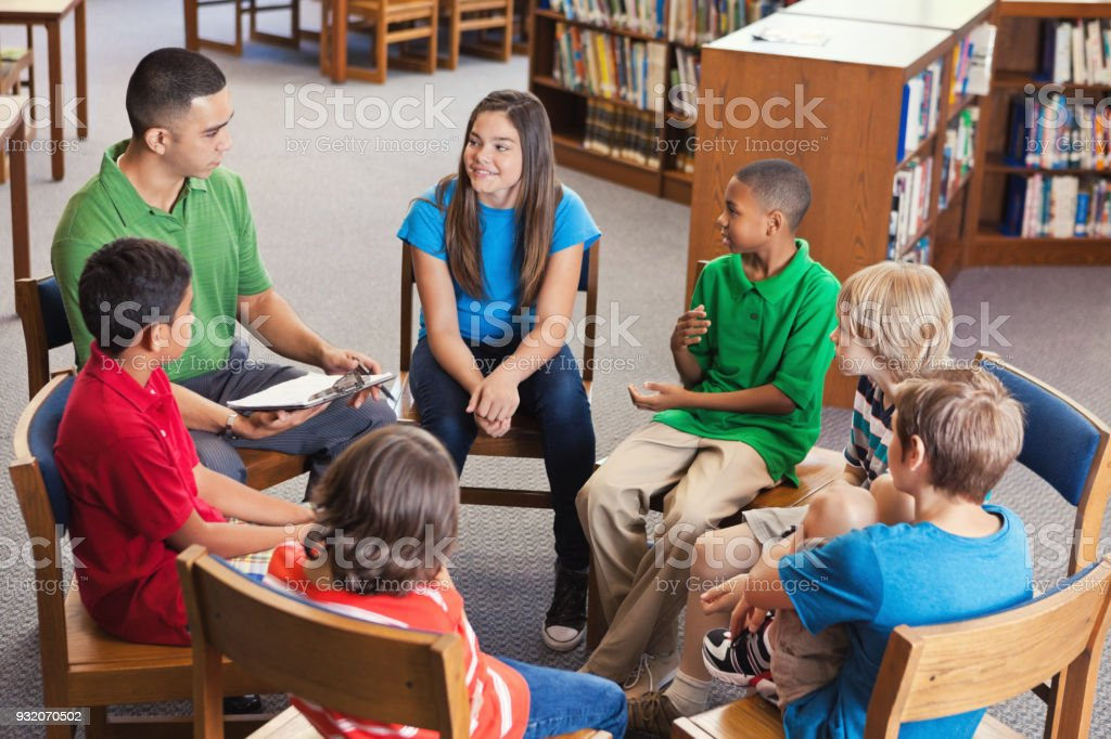 若い先生のリード図書館の学校クラブの後 ストックフォト