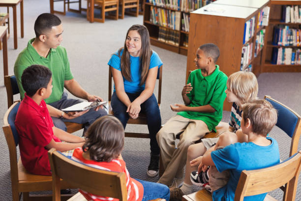 young teacher leads after school club in library - middle school teacher stock pictures, royalty-free photos & images