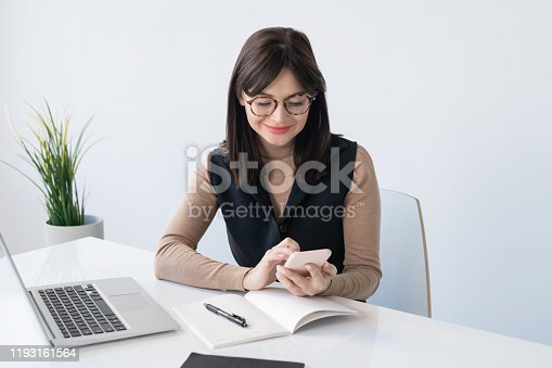 Young teacher or businesswoman with smartphone over open copybook looking for contact while sitting by desk in front of laptop