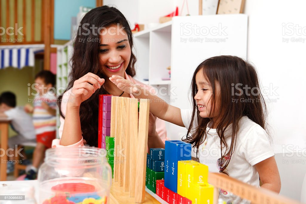 Young teacher playing with cute little girl stock photo