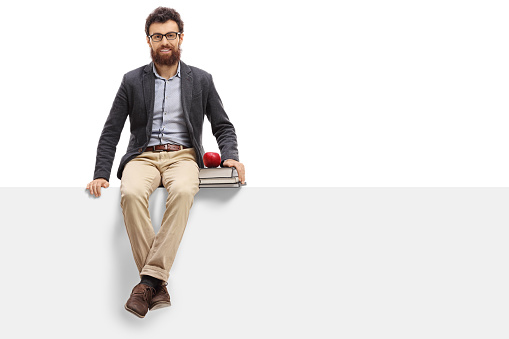 istock Young teacher sitting on panel and looking at the camera 646931010