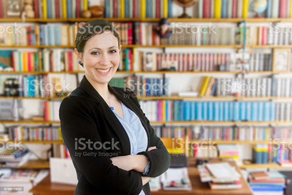 Young teacher standing in front of a bookcase stock photo