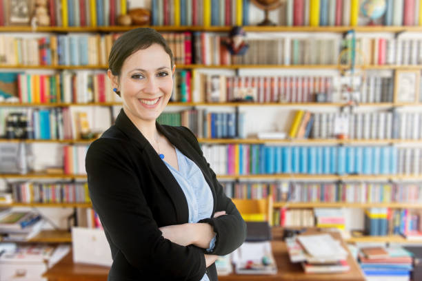 young teacher standing in front of a bookcase - professor stock photos and pictures