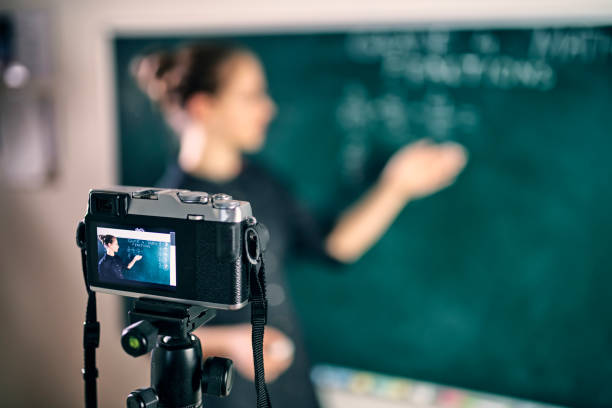Young teacher teaching remotely using camera to stream lesson stock photo