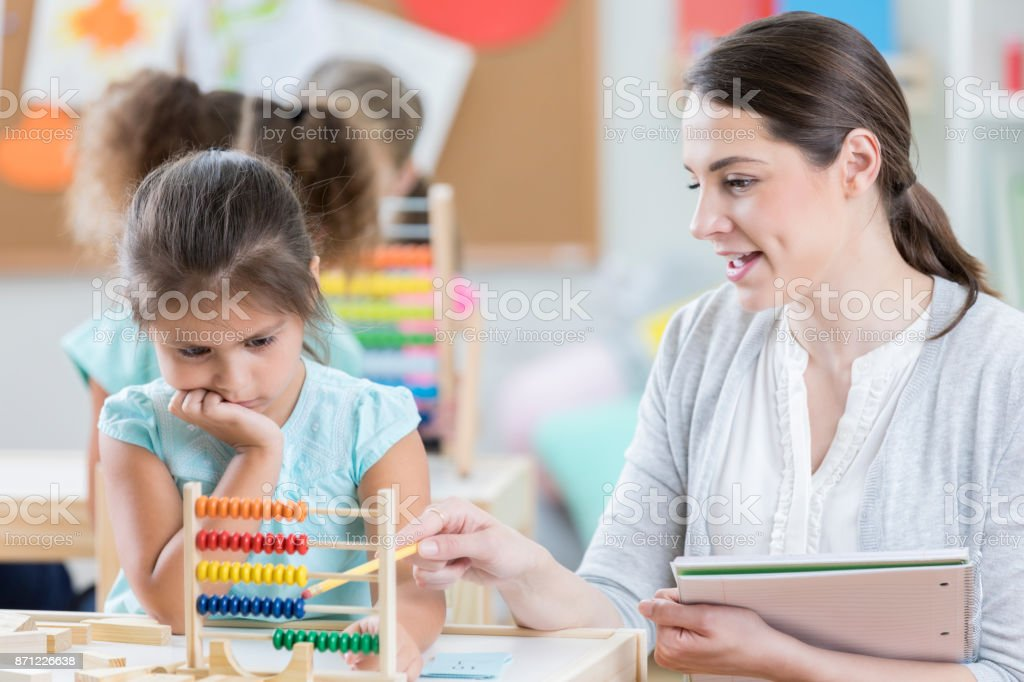 A young teacher sits at a table with a little girl and points to an...