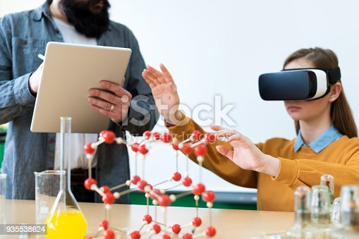 istock Young teacher using Virtual Reality Glasses and 3D presentation to teach students in chemistry class. Education, VR, Tutoring, New Technologies and Teaching Methods concept. 935538624