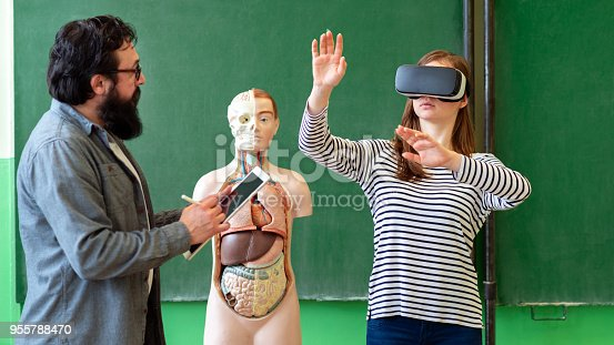 istock Young teacher using Virtual Reality Glasses and 3D presentation to teach students in biology class. Education, VR, Tutoring, New Technologies and Teaching Methods concept. 955788470