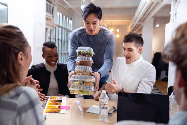 ungt team äta på kontoret på lunchrasten - lunchrast bildbanksfoton och bilder