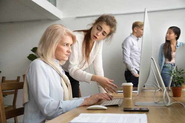 Young team leader correcting offended senior employee scolding for mistake stock photo