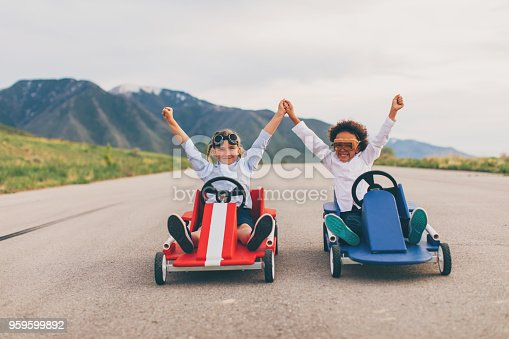 Young business girls dressed in business attire and race goggles in push carts down a rural road in Utah. These business children love racing and competing and working together for the success of their business. They give raised hands in victory at the finish line.