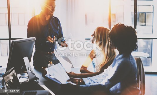 istock Young team of coworkers making great meeting discussion in modern sunny office.Teamwork concept.Hispanic businessman talking with two colleague woman.Horizontal,blurred background,flare effect. 912141572