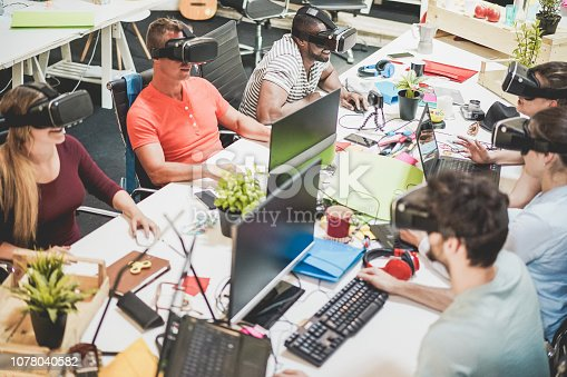 istock Young teamwork using virtual reality glasses in creative office - Co-workers trying new technology devices at work - Business, marketing and tech trends concept - Focus on left black man headset 1078040582
