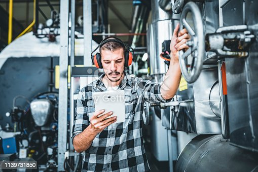 Maintenance Engineer is Inspecting the Boiling System at the Heating Plant. He is Standing in the Basement of the Power Station and Doing Quality Control While Tightening the Valve of the Heating System and Looking at his Digital Tablet.