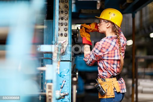 Young woman in uniform repairing something with screwdriver