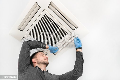 istock Young technician repairing air conditioner 1159486233