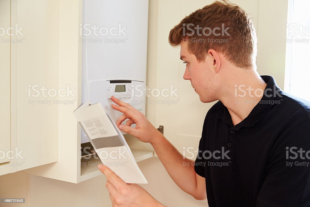 Young technician servicing a boiler, consulting manual stock photo