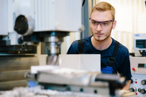 young technician works at a milling machine stock photo