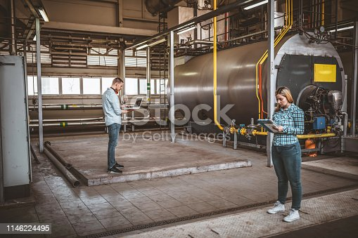 Handsome Maintenance Engineer is Inspecting the Boiling System at the Heating Plant with his Beautiful Female Coworker. They are Standing in the Basement of the Power Station with Protective Headphones and are Doing Quality Control and Looking at They Digital Devices. Concept of Teamwork.