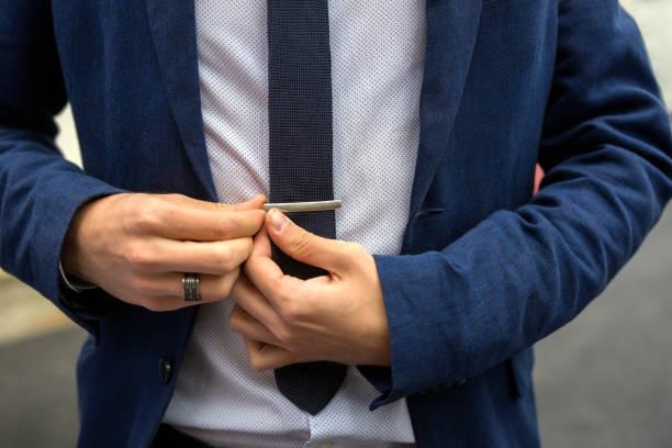 teen junge lässig gekleidet behebt seine krawatte nadel - krawattennadel stock-fotos und bilder