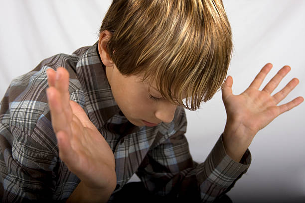 Young teen boy with arms up in praise stock photo