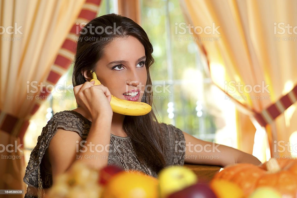 Young teen eats fruits on the living room table stock photo