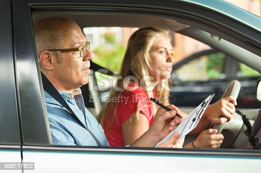 A teenager young girl in the process of taking the driver examination for driver's license. She is carefully driving while the examiner is scoring her driving skill.