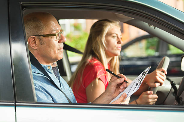 Young Teen Girl Doing Driving Exam with Examiner A teenager young girl in the process of taking the driver examination for driver's license. She is carefully driving while the examiner is scoring her driving skill. driving instructor stock pictures, royalty-free photos & images