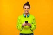 istock Young teen girl in neon green sweatshirt and glasses, holding smartphone in hands, using app or going to text friends, isolated on yellow background 1257722846
