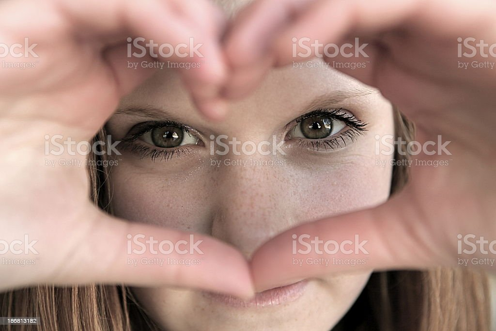 Young Teen Girl Looking Through Heart Shape royalty-free stock photo